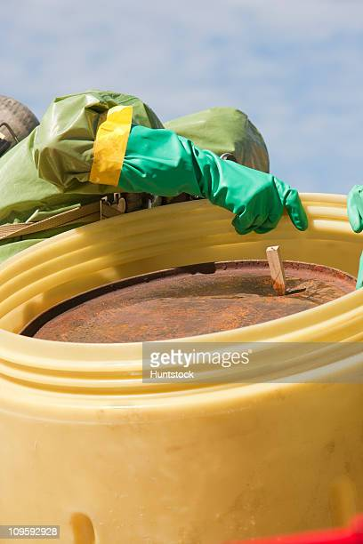HazMat firefighter putting a plugged drum into a salvage drum