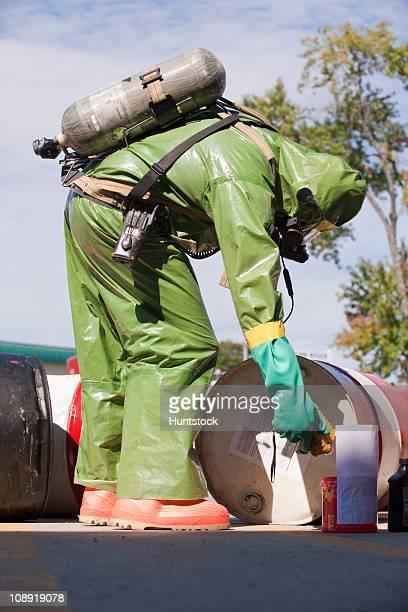 HazMat firefighter using sensing meter for examining gas levels