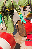 HazMat firefighters plugging a drum