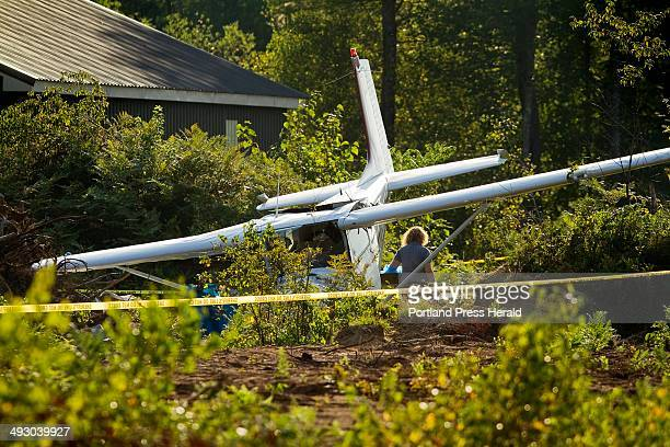 Hazmat personel walk away after cleaning a fuel spill from the scene of a single engine Cessna 172 crash at Limington Harmon Airport in Limington on...