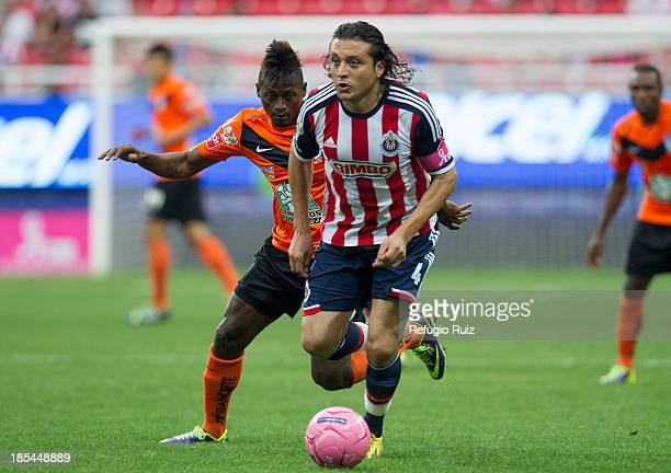 Héctor Reynoso of Chivas fights for the ball with Duvier Riascos of Pachuca during the match between Chivas and Pachuca as part of the Apertura 2013...