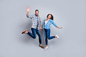 He and She full length portrait of attractive, playful, cheerful, couple in casual outfit, hold hands, jumping  over grey background, valentine day, 14 february