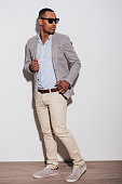Confident young African man in smart casual clothing looking over shoulder while standing against white background