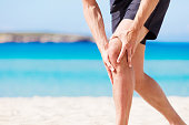 A male jogger with sudden knee-pain at the beach. XXXL size image. Image taken with Canon EOS 5Ds and EF 70-200mm USM L 2,8.