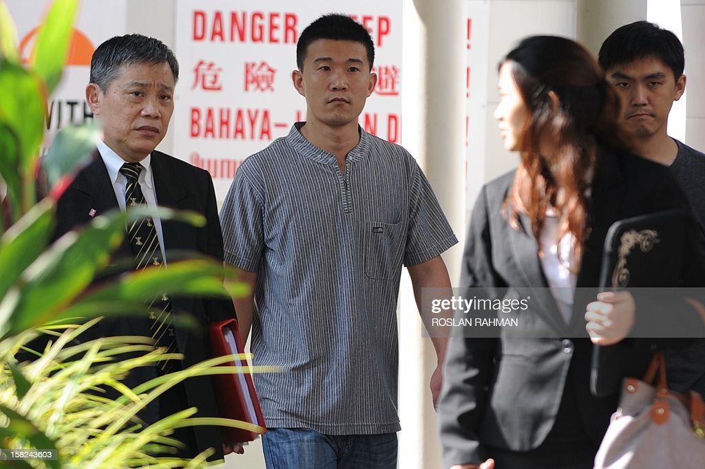 He Jun Ling (2nd L), 32, one of four Chinese bus drivers facing possible jail for instigating Singapore's first industrial strike in 26 years, arrives at the subordinate courts with his lawyer in Singapore on December 12, 2012. Four Chinese bus drivers facing possible jail were given more time on December 12 to explore their legal options and were told to report again on December 19 for a new pre-trial conference.