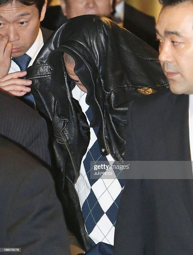 He Liang (C), surrounded by Japanese policemen, arrives at the Narita international airport in Narita, suburban Tokyo from Canada on November 15, 2013 after he was arrested in Toronto. A 43-year-old Chinese man was extradited to Japan from Canada Friday for passport control violation as police hope he could shed light on the 1995 triple shooting murder in Tokyo. In July 1995, three female workers were shot point-blank in the head and died in the office of a supermarket in western Tokyo.
