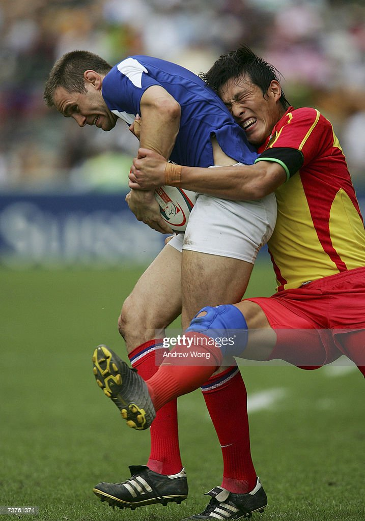 He Zhongliang of China tackles Jeremy Fleurus of France during their Bowl Quarter Final at the Cathay Pacific/Credit Suisse Hong Kong Rugby Sevens on...
