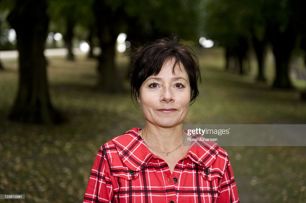 Head and shoulder portrait of Danish woman, 53 years old, in a red, plaid coat at Frederiksberg Park, Copenhagen, Denmark