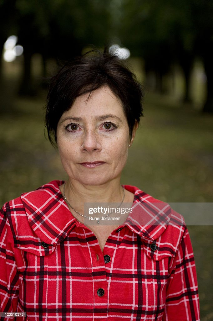 Head and shoulder portrait of Danish woman, 53 years old, in red, plaid coat at Frederiksberg Park, Copenhagen, Denmark