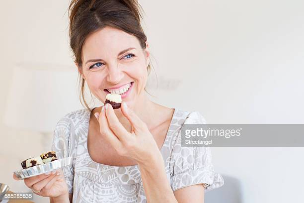 Head and shoulders of mature woman holding sweet baked goods, looking away smiling