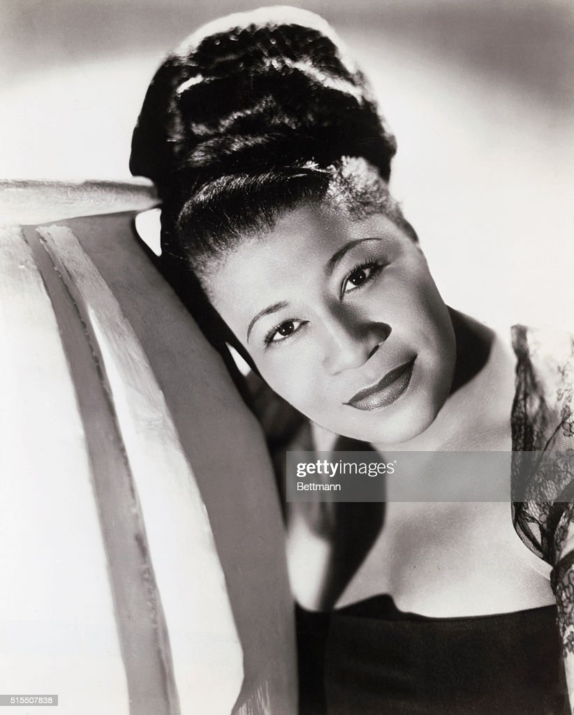 Head and shoulders photo of a young Ella Fitzgerald, wearing her hair up in a large bun and leaning to the left.