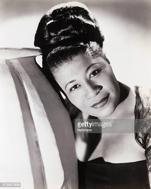 Head and shoulders photo of a young Ella Fitzgerald wearing her hair up in a large bun and leaning to the left