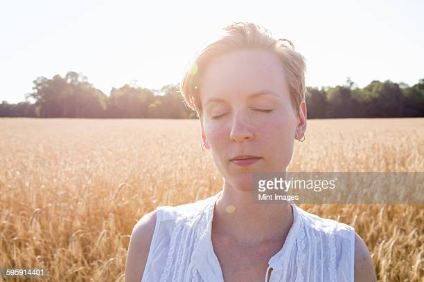 Head and shoulders portrait of a young woman standing in a cornfield.
