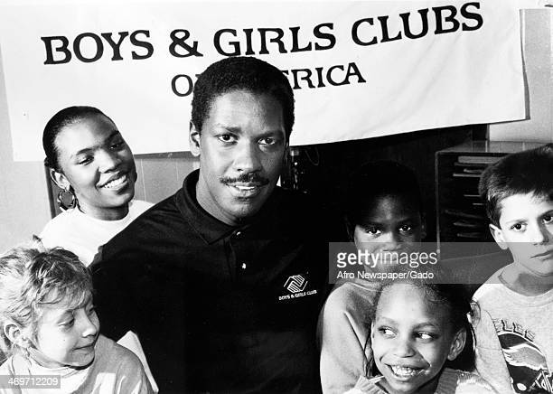 A head and shoulders portrait of actor Denzel Washington with a group of children from the Boys Girls Clubs of America 1993