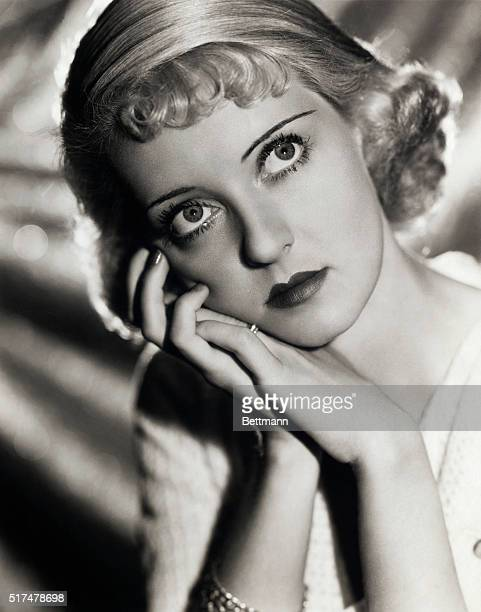 Head and shoulders portrait of Bette Davis with short blonde curled hair with her head resting on her hands with a faraway look in her eyes Undated...