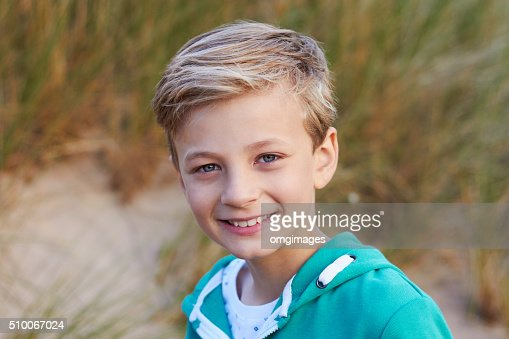 Head And Shoulders Portrait Of Boy By Sand Dunes : Stock Photo