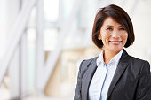 Head and shoulders portrait of smiling Asian businesswoman
