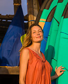 head and shoulders portrait of young beautiful and happy blond woman smiling relaxed and cheerful posing with colorful surf boards leaning in surfboard in beauty fashion summer concept