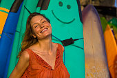 head and shoulders portrait of young beautiful and happy blond woman smiling relaxed and cheerful posing with colorful surf boards in the background in beauty fashion and summer holidays concept