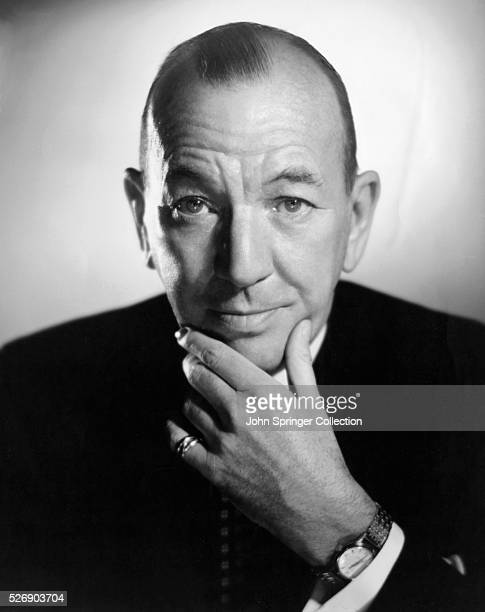 Head and shoulders portrait photo of British actor Noel Coward with his hand massaging his chin Ca 1950