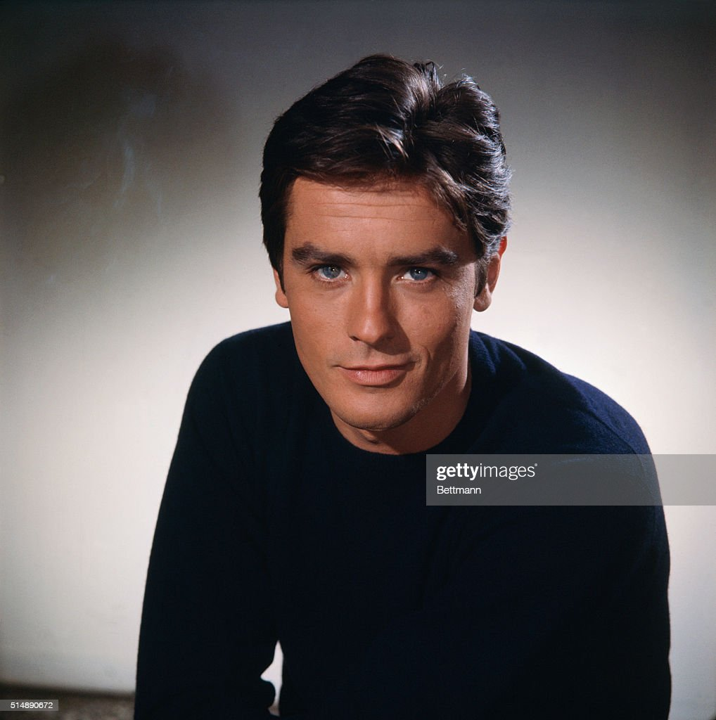 Head and shoulders portrait photo of French actor <a gi-track='captionPersonalityLinkClicked' href=/galleries/search?phrase=Alain+Delon&family=editorial&specificpeople=228460 ng-click='$event.stopPropagation()'>Alain Delon</a> (1935-) smiling in a black sweater. Ca. 1960s.