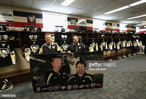 Head Athletic Trainer Chris Stewart and Equipment Manager Dana Heinze of the Pittsburgh Penguins pose with a picture of themselves in the locker room...
