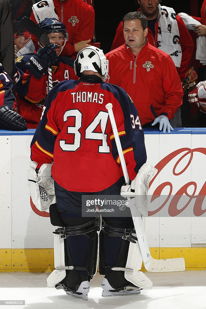 Head athletic trainer David Zenobi talks to Tim Thomas #34 of the Florida Panthers late in the third period of the game against the Chicago Blackhawks at the BB&T Center on October 22, 2013 in Sunrise, Florida. Thomas came out of the game with an injury. The Blackhawks defeated the Panthers 3-2 in a shoot-out.
