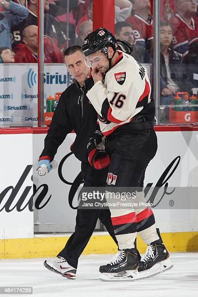 Head Athletic Trainer Gerry Townend helps Clarke MacArthur of the Ottawa Senators off the ice against the Montreal Canadiens during an NHL game at...