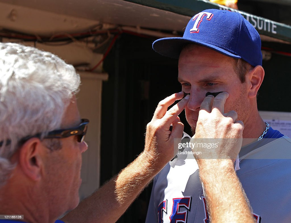Head Athletic Trainer Jamie Reed applies eye black to Josh Hamilton #32 of the Texas Rangers in the dugout before the game against the Oakland Athletics at O.co Coliseum on August 14, 2011 in Oakland, California.