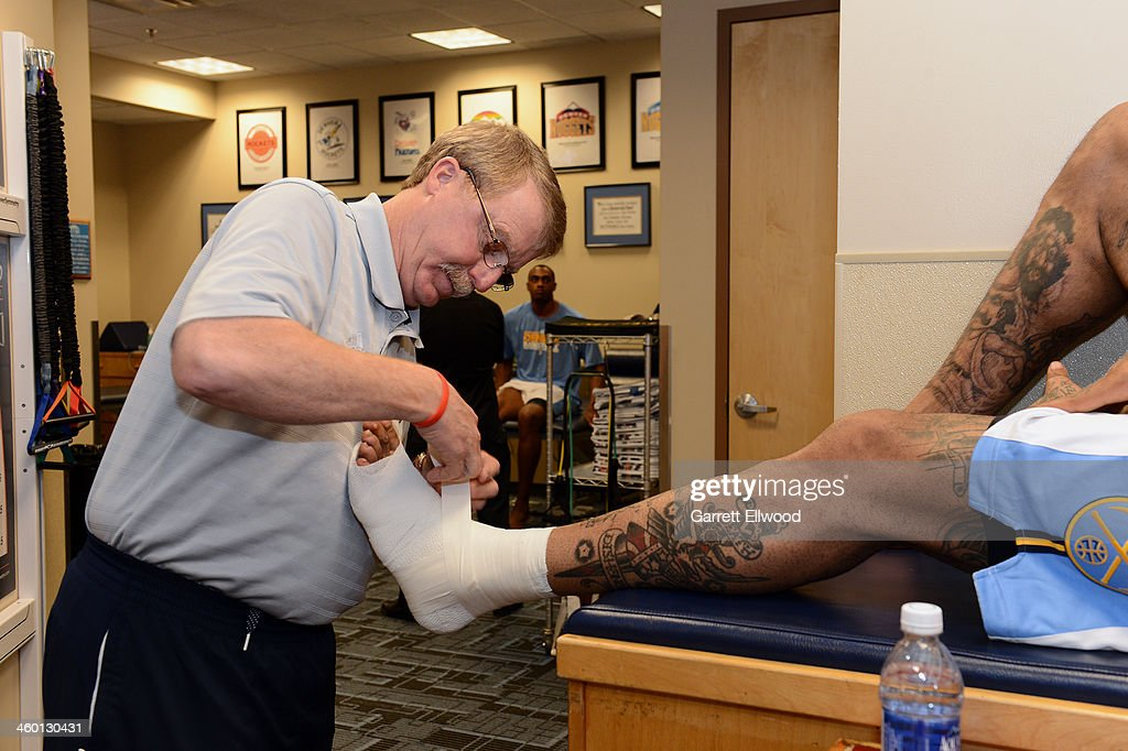 Head Athletic Trainer Jim Gillen tapes the ankle of Wilson Chandler #21 of the Denver Nuggets prior to the game against the Philadelphia 76ers on January 1, 2014 at the Pepsi Center in Denver, Colorado.
