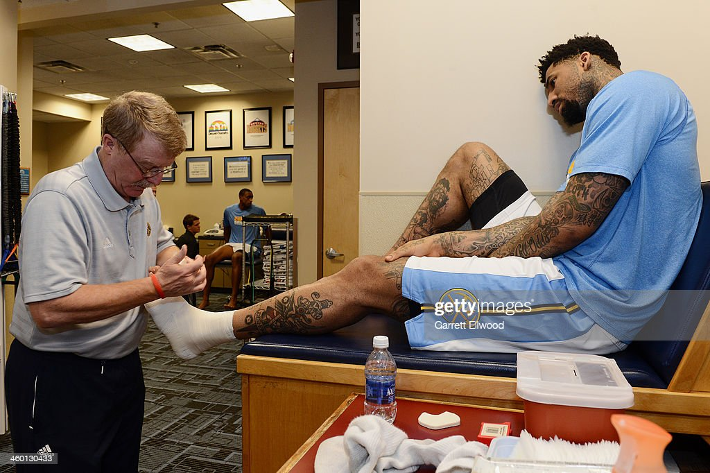 Head Athletic Trainer Jim Gillen tapes the ankle of Wilson Chandler of the Denver Nuggets prior to the game against the Philadelphia 76ers on January...