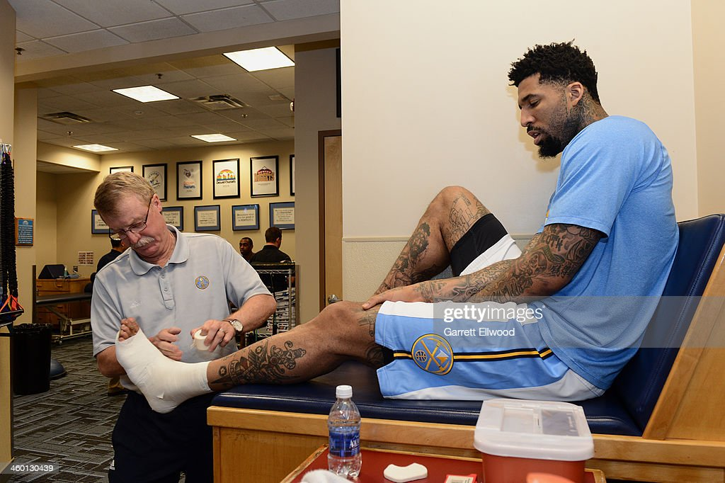 Head Athletic Trainer Jim Gillen tapes the ankle of <a gi-track='captionPersonalityLinkClicked' href=/galleries/search?phrase=Wilson+Chandler&family=editorial&specificpeople=809324 ng-click='$event.stopPropagation()'>Wilson Chandler</a> #21 of the Denver Nuggets prior to the game against the Philadelphia 76ers on January 1, 2014 at the Pepsi Center in Denver, Colorado.