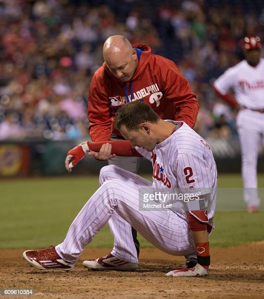 Head athletic trainer Scott Sheridan of the Philadelphia Phillies helps up Tyler Goeddel after he was hit in the head with a pitch in the bottom of...