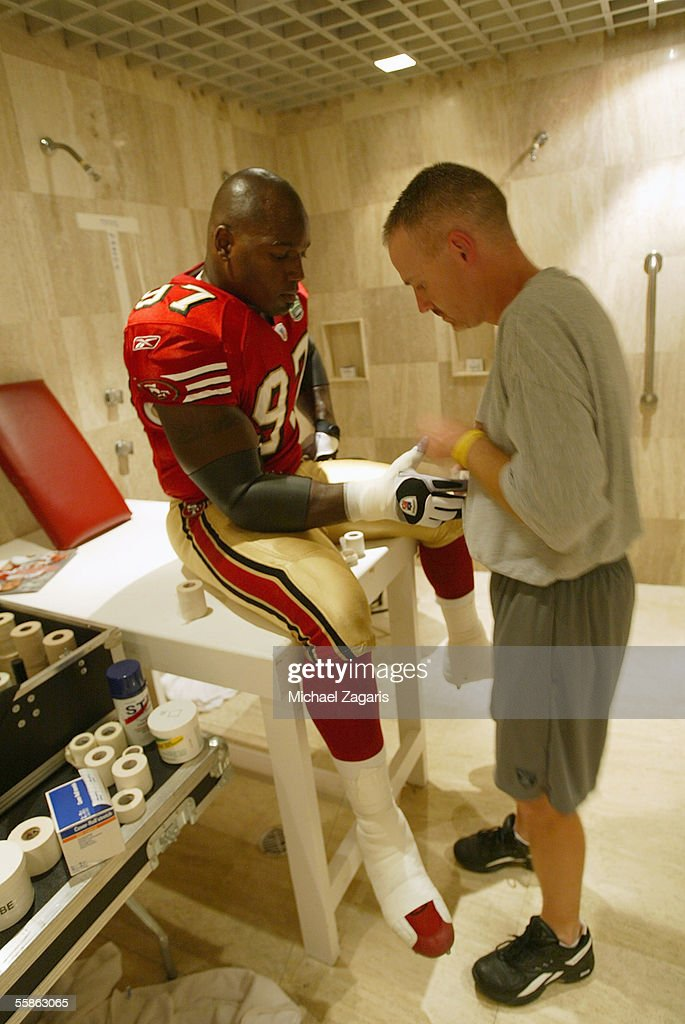 Head athletic trainer Todd Lazenby tapes Bryant Young #97 of the San Francisco 49ers in the locker room before the game against the Arizona Cardinals at Estadio Azteca on October 2, 2005 in Mexico City, Mexico.
