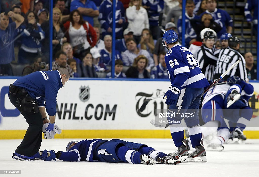 Head athletic Trainer Tom Mulligan (L) and <a gi-track='captionPersonalityLinkClicked' href=/galleries/search?phrase=Steven+Stamkos&family=editorial&specificpeople=4047623 ng-click='$event.stopPropagation()'>Steven Stamkos</a> #91 of the Tampa Bay Lightning attend to <a gi-track='captionPersonalityLinkClicked' href=/galleries/search?phrase=Mike+Kostka&family=editorial&specificpeople=2193393 ng-click='$event.stopPropagation()'>Mike Kostka</a> #21 during action against the Montreal Canadiens at the Tampa Bay Times Forum on April 1, 2014 in Tampa, Florida.