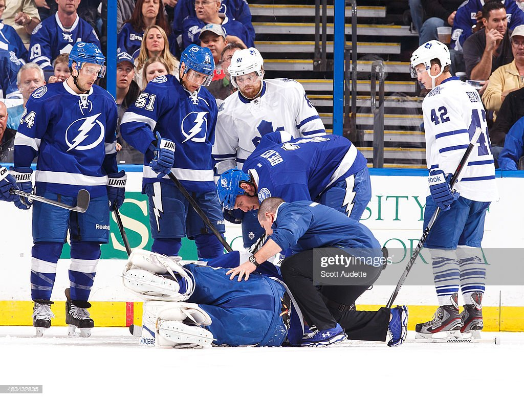 Head athletic trainer Tom Mulligan tends to goalie Ben Bishop #30 of the Tampa Bay Lightning after he sustained an injury during the first period against the Toronto Maple Leafs at the Tampa Bay Times Forum on April 8, 2014 in Tampa, Florida.