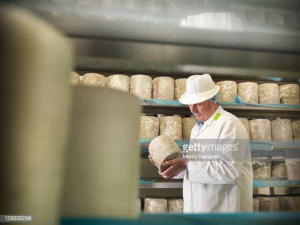 Head cheese-maker with blue cheese in cheese-making factory