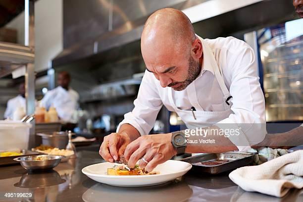 Head chef finishing dish in kitchen at restaurant