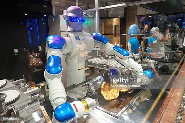 Head chef robot 'Andrew' flips the Okonomiyaki Japanese pancake in the 'Hen na Restaurant ' during the 'Kingdom of Robot' press preview at the Huis...