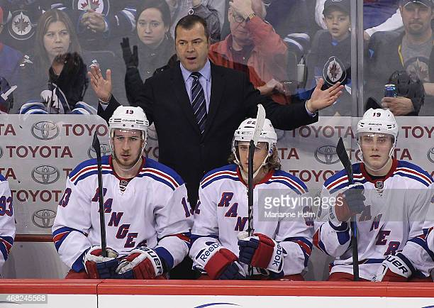 Head coach Alain Vigneault of the New York Rangers gestures from the bench in third period action in an NHL game against the Winnipeg Jets at the MTS...