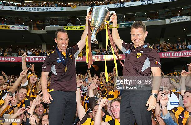 head coach Alastair Clarkson and assist and Brendon Bolton of the Hawks celebrates with the Premeirship Cup during the 2014 AFL Grand Final match...