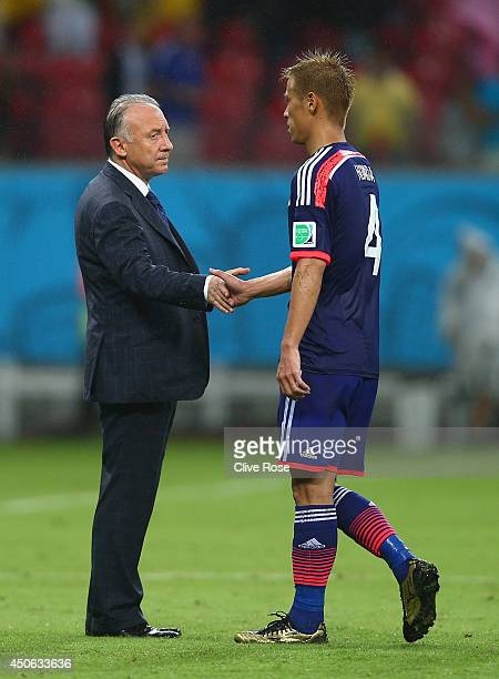 Head coach Alberto Zaccheroni of Japan shakes hands with Keisuke Honda after being defeated by the Ivory Coast 21 during the 2014 FIFA World Cup...