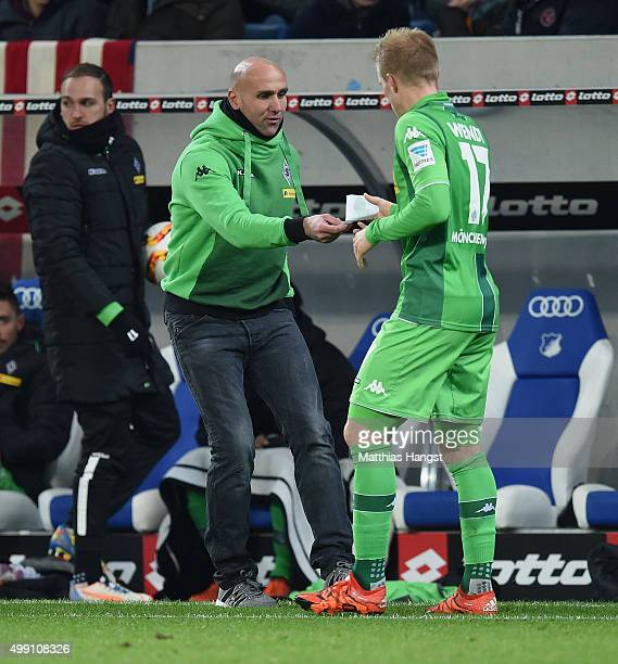 Head coach Andre Schubert of Gladbach hands over a piece of paper to Oscar Wendt of Gladbach during the Bundesliga match between 1899 Hoffenheim and...