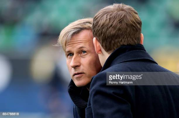Head coach Andries Jonker of Wolfsburg chats with sporting director Olaf Rebbe of Wolfsburg prior to the Bundesliga match between VfL Wolfsburg and...
