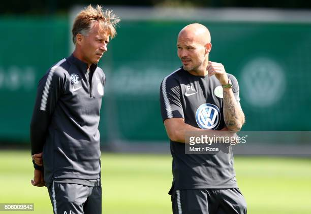 Head coach Andries Jonker talks to assistant coach Fredrik Ljungberg during a training session at Volkswagen Arena on July 3 2017 in Wolfsburg Germany