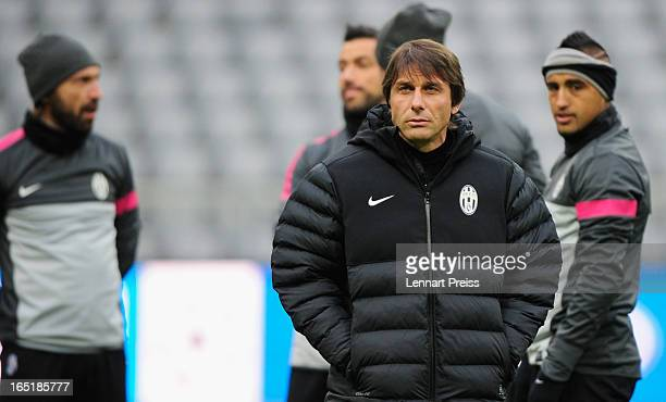 Head coach Antonio Conte of Juventus looks on next to Andrea Pirlo and Arturo Vidal during a training session prior to the Champions League...
