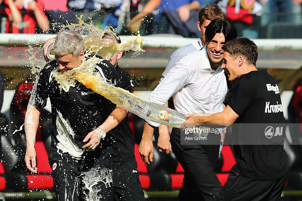Head coach Armin Veh of Frankfurt is showered with beer by Marc Stendera and Stefano Celozzi after the Bundesliga match between Eintracht Frankfurt...