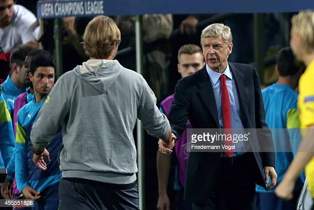 Head coach Arsene Wenger of Arsenal speaks with head coach Juergen Klopp of Borussia Dortmund during the UEFA Champions League Group D match between...