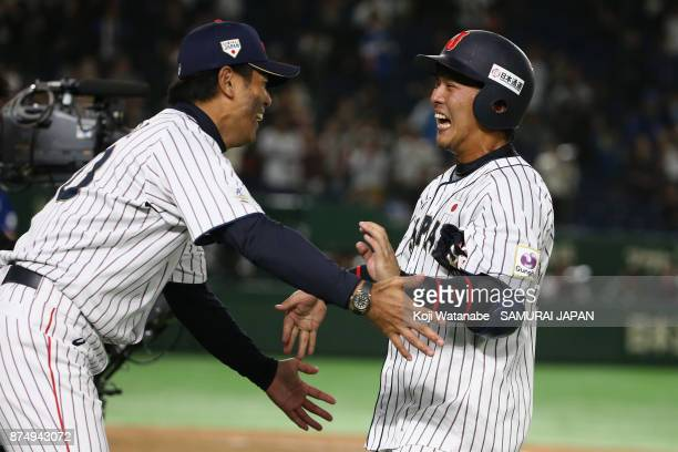 Head coach Atsunori Inaba of Japan congratulates Catcher Tatsuhiro Tamura of Japan after his gameending double in the bottom of tenth inning during...