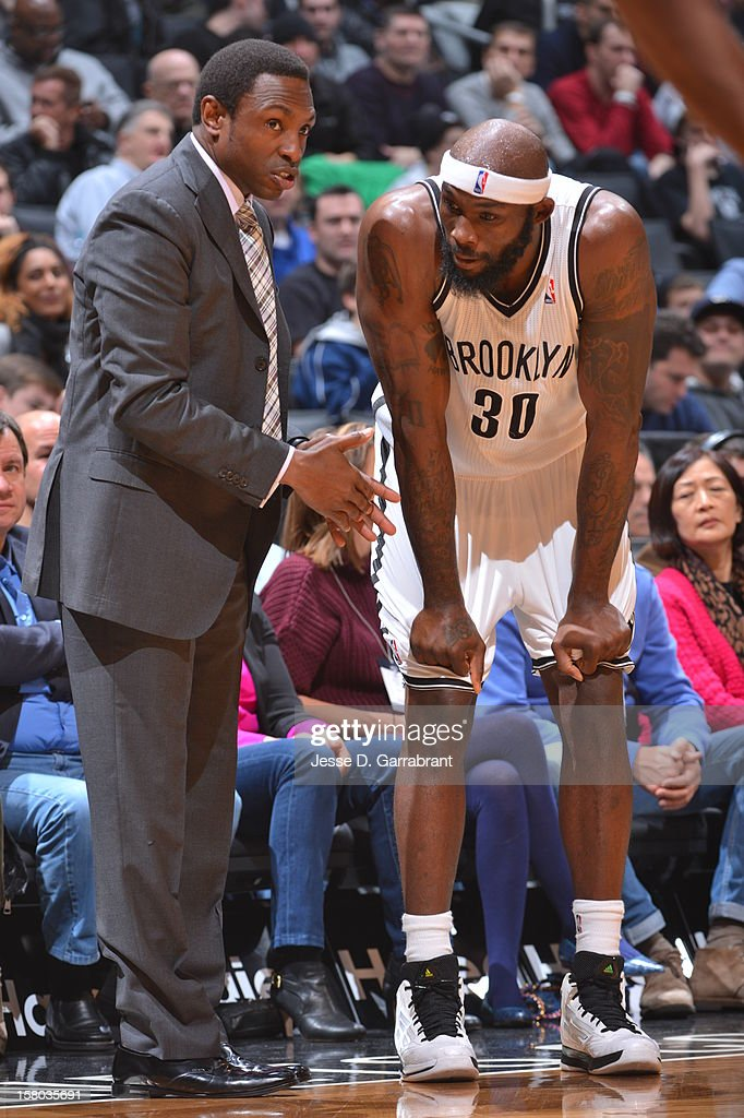Head coach Avery Johnson and Reggie Evans #30 of the Brooklyn Nets talk during the game against the Milwaukee Bucks at the Barclays Center on December 9, 2012 in Brooklyn, New York.